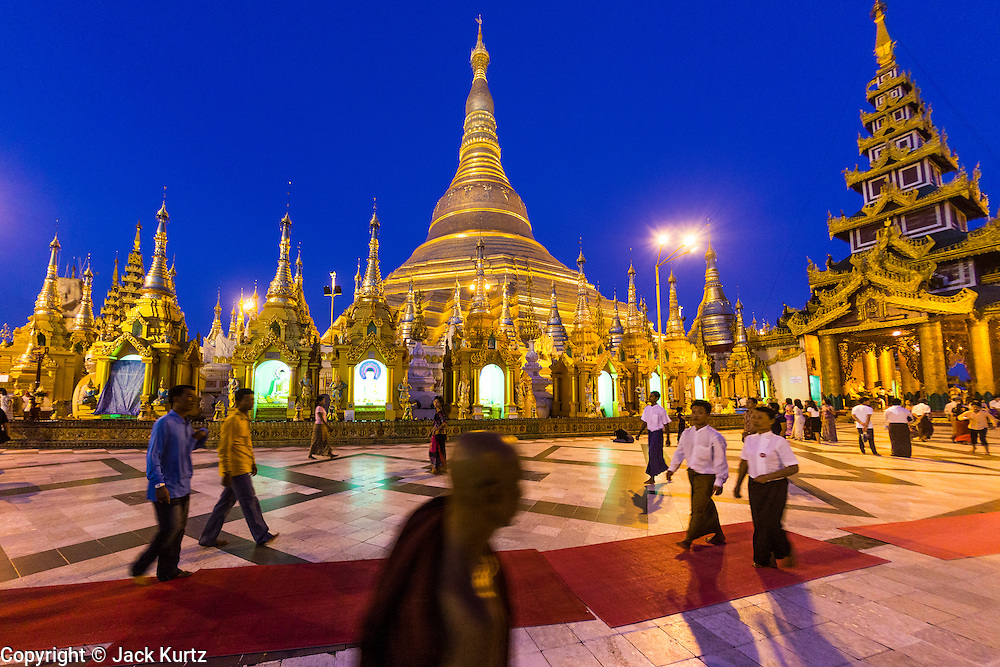 15 JUNE 2013 - YANGON, MYANMAR: Shwedagon Pagoda in the evening. Shwedagon Pagoda is officially known as Shwedagon Zedi Daw and is also called the Great Dagon Pagoda or the Golden Pagoda. It is a 99 meter (325ft) tall pagoda and stupa located in Yangon, Burma. The pagoda lies to the west of on Singuttara Hill, and dominates the skyline of the city. It is the most sacred Buddhist pagoda in Myanmar and contains relics of the past four Buddhas enshrined: the staff of Kakusandha, the water filter of Koṇāgamana, a piece of the robe of Kassapa and eight strands of hair from Gautama, the historical Buddha. Burmese believe the pagoda was established as early ca 540BC, but archaeological suggests it was built between the 6th and 10th centuries. The pagoda has been renovated numerous times through the centuries. Millions of Burmese and tens of thousands of tourists visit the pagoda every year, which is the most visited site in Yangon.  PHOTO BY JACK KURTZ
