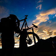 "Chris ""Canguro"" Theobald loading bikes into his pickup truck at sunset. Riding the singletrack of Lake Sophia park outside of Torres del Paine National Park in Chile."