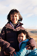 Two Asian sisters hug and smile at the camera with the Moffat hills in the bakcground on a hazy sunny day.