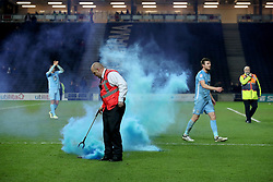A steward picks up a flare after the final whistle of the Emirates FA Cup  Fourth Round match at  Stadium MK Milton Keynes.