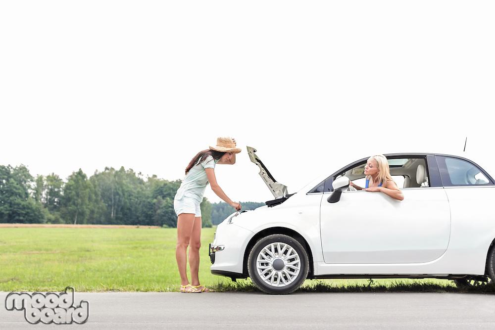 Woman looking at friend repairing broken down car on country road
