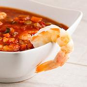 Bowl of shrimp gumbo, in a light, bright white summer setting.