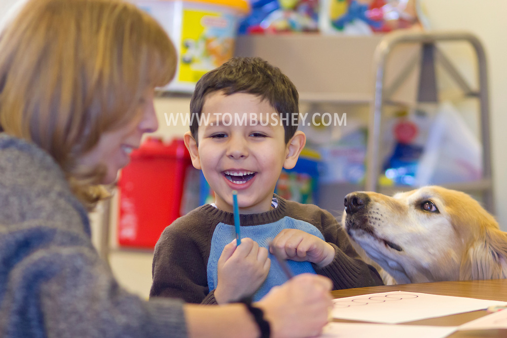 "Middletown, New York - Hope Roche and her therapy dog Lu work with a child during a ""Getting Ready for Kindergarten"" program at Thrall Library on Jan. 30, 2014."