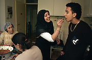 Dutch-Turkish teenager Hakan Dinc is fed by his aunt while his female family members cook at home in Amsterdam. .Dinc, 16, was born in the Netherlands. His grandparents from his father?s side came from Turkey in 1971, and his mother came in 1987. Dinc feels more Turkish than Dutch, most of his friends are Turkish and he wants to marry a Turkish girl. During his time off he works in his uncle?s grocery store. Later, he wants to have his own shop. Dinc is following a Commerce course at a vocational school in Amsterdam. .Dinc likes music, pool and chilling out. He has a fourteen-year-old sister and a brother aged ten months. .Picture shot in Amsterdam in 2004 by Justin Jin. .