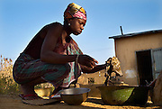 Natitingou November 2006 - Beninese woman preparing food over a fire in front of her house in Natitingou, In Benin .