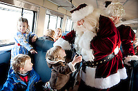 Much to the delight and amazement of Violet Rohelia and Cole Johnson Essie Corrow chats with Santa Claus while onboard the train Sunday afternoon.  (Karen Bobotas/for the Laconia Daily Sun)