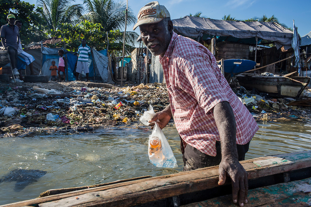 Fisherman Jean Claude Pierre leaves his boat after checking his nets on Monday, December 15, 2014 in Port-au-Prince, Haiti.
