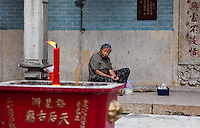 Old woman sitting in front of Tin Hau Temple as candle and incense offerings burn.