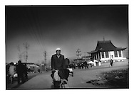 Hui Chinese Muslim man rides past mosque which is built in the Chinese temple style, near Linxia, China.  Islam arrived here via Persian traders traveling along the Silk Road, which came through Linxia.