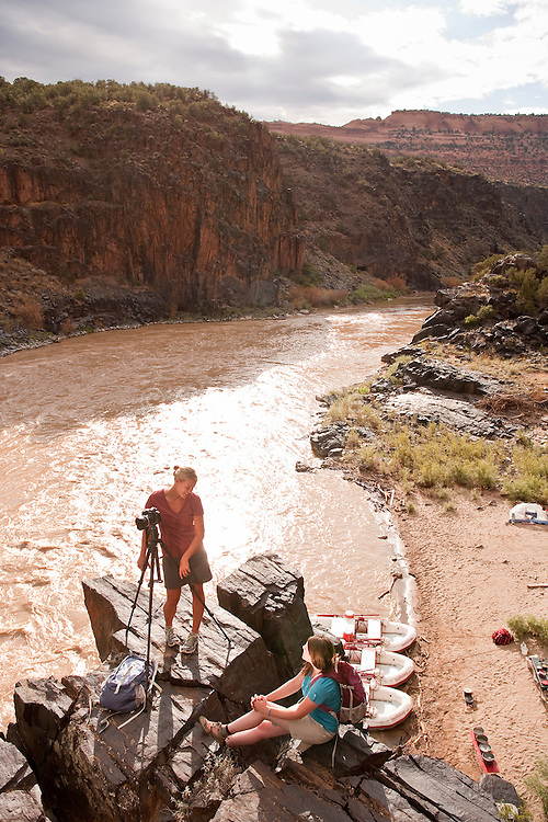 Kate Harvey & Kristina LaBouff take photographs on an overlook above their  camp on the Colorado River in Westwater Canyon Utah.
