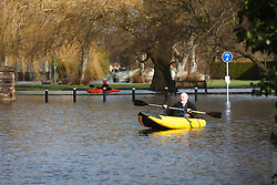 © Licensed to London News Pictures. 09/02/2014. Winchester, Hampshire, UK. A man in his inflatable kayak on Park Avenue in Winchester. Water levels rose overnight in parts of the historic city where a flood warning has been issued by the Environment Agency for parts of the River Itchen. Photo credit : Rob Arnold/LNP