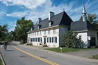 Road Cyclist Biking Past Historic Manoir Mauvide-Genest, Saint-Jean-de- I'ile-d'Orleans, Quebec, Canada