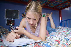 Teenage girl lying on her bed with mobile phone and writing,