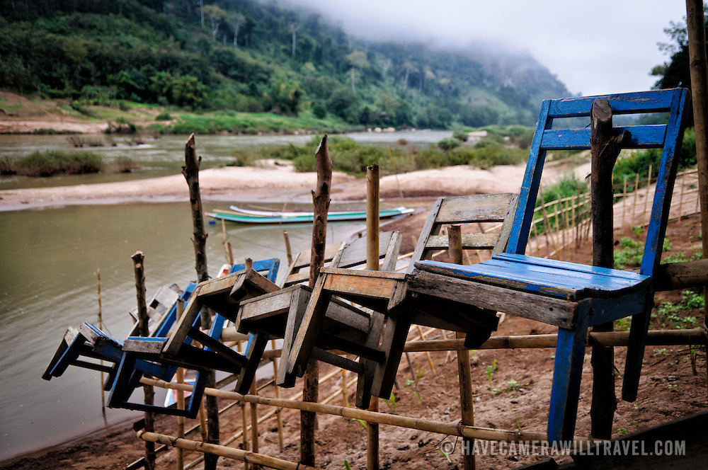 A group of wooden chairs are suspended on wooden stakes surrounding a small vegetable garden plot on the banks of the Nam Ou (River Ou) in Nong Khiaw in nothern Laos. In the background, morning mists still obscure some of the rugged terrain of the surrounding countryside.
