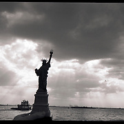Statue of Liberty in New York Harbor with Tugboat and Dramatic skyline