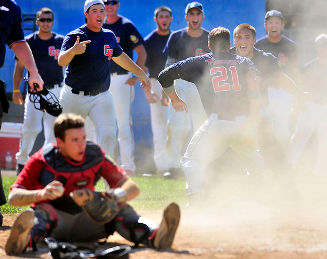 Greater Pittston Area Legion celebrates as Swoyersville catcher Ryan Hogan sits at home plate.