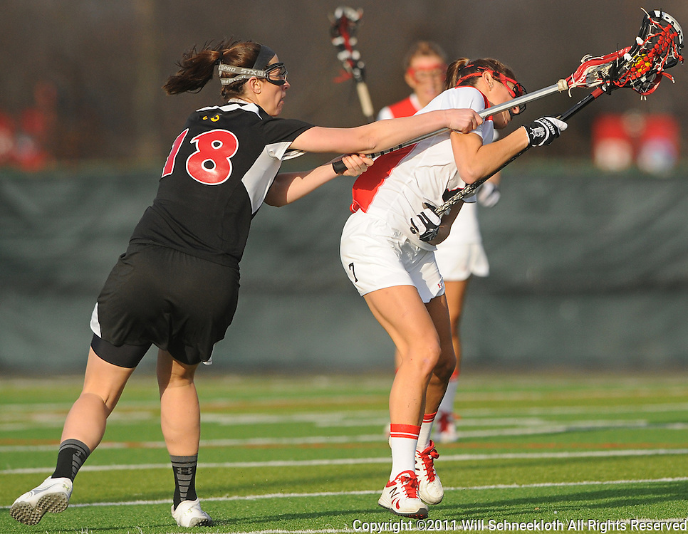 Temple senior midfielder Jackie Mercer stick-checks Rutgers senior midfielder Ali Steinberg. Temple defeated Rutgers 12-11 in NCAA women's college lacrosse at the Rutgers Turf Field in Piscataway, N.J.
