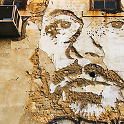 Street art by Alexandre Farto (Vhils) at an old warehouse