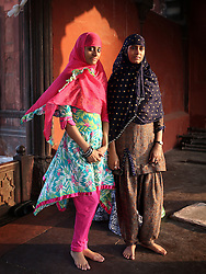 © Licenced to London News Pictures. 26//11/2014. Delhi. India.  <br /> Two muslim girls are pictured at dusk in the courtyard of the Jama Masjid mosque in Old Delhi, India, November 26th 2014. Commissioned by the Mughal Emperor Shah Jahan, it is the best-known mosque in India.<br /> Photo Credit: Susannah Ireland