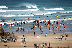 © Licensed to London News Pictures. 30/07/2020. Perranporth, UK. People enjoy the hot weather on Perranporth Beach, Cornwall, on a very hot day in the southwest. Temperatures are set to rise to 22 degrees Celsius by the afternoon. Photo credit : Tom Nicholson/LNP
