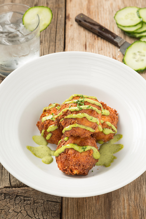 Cheddar Fritters with fire roasted jalapeno aioli on a rustic background.