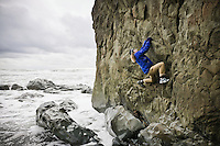 A woman bouldering on a sea stack on Rialto beach on the coast of Washington, USA.