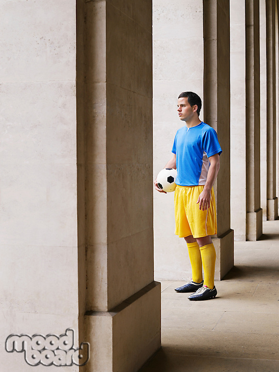 Soccer player holding ball standing in portico