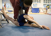 A coach helps a young gymnast to stretch in an afternoon training session of the Beijing Gymnastic team.