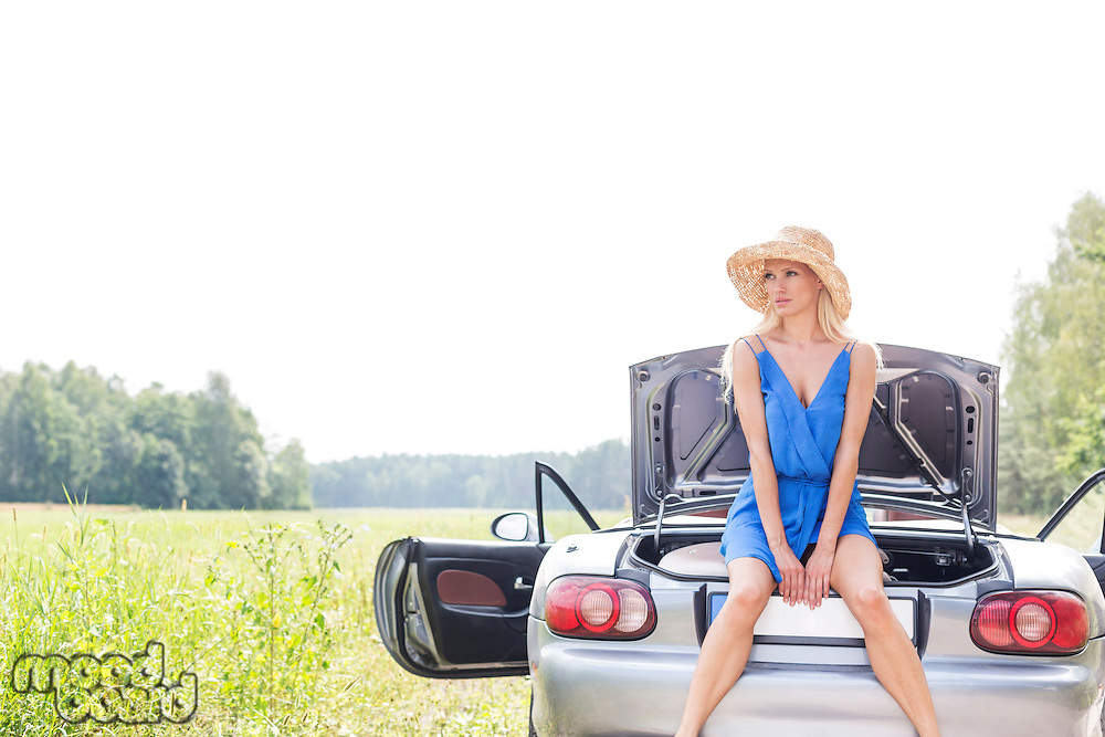 Young woman sitting on convertible trunk against clear sky