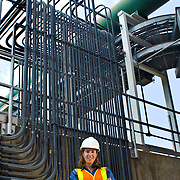 A female civil engineer, wearing a hard hat and a reflective orange vest,  standing in front of a water filtration system in Chapel Hill, NC.