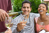 Couple drinking wine with friends outdoors