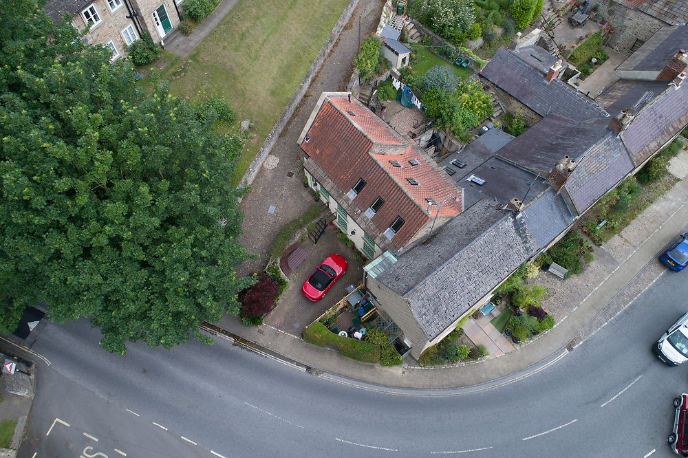 Overview of shiny red car standing in driveway of historic home, of Richmond, Yorkshire, England