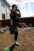 A Young kid talking on a mobile phone and playing football in the garden, Aberdeen, Scotland 2005