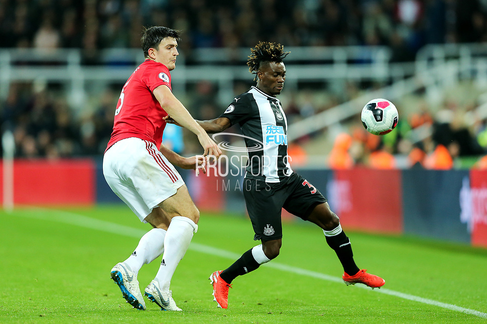 Christian Atsu (#30) of Newcastle United attempts to control the ball on the touch line under pressure from Harry Maguire (#5) of Manchester United during the Premier League match between Newcastle United and Manchester United at St. James's Park, Newcastle, England on 6 October 2019.