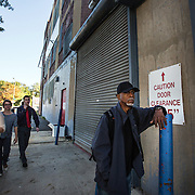WASHINGTON, DC-OCT14: Leon Savoy, waits for Capital Self-Storage to open, October 16,  2015, as passersby head to work. Savoy  will get different clothes from his before heading to his job as a furniture restorer. Savoy is currently homeless and living at a nearby shelter. Many of the area homeless have possessions they want to keep safe, just nowhere permanent to live, so they store their belongings at Capital Self-Storage, where an upper-level unit costs $30/month. Some of the homeless patrons also spend their days in their storage units, when shelters are closed during midday hours. The storage facility near 3rd and Florida Avenue in Northeast, Washington, DC, is about to be replaced by a boutique hotel. (Photo by Evelyn Hockstein/For The Washington Post)