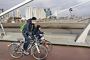 In Rotterdam fietsen twee kinderen tegen de wind in de Erasmusbrug omhoog.<br /> <br /> In Rotterdam cyclists are riding the Erasmus bridge with a severe head wind.