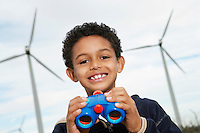 Boy (7-9) holding binoculars at wind farm, portrait