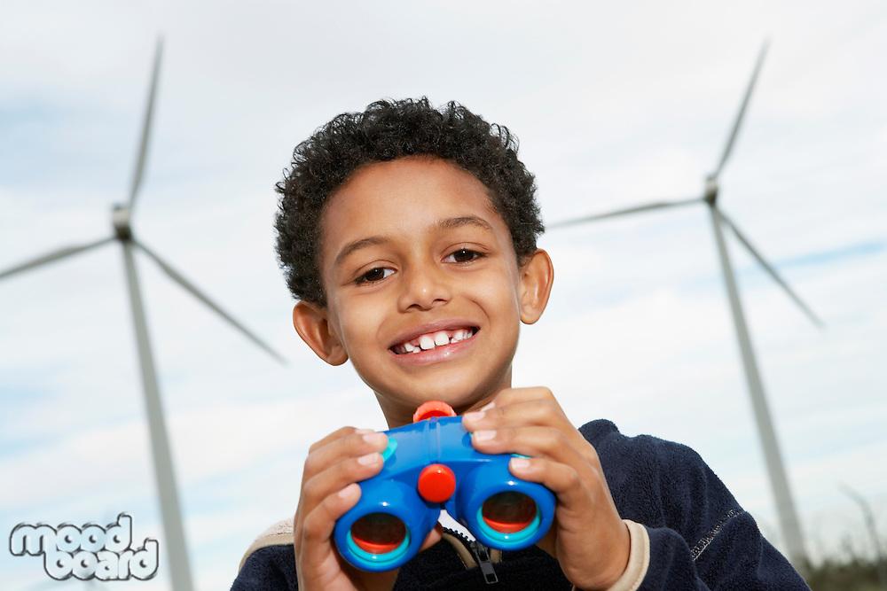 Boy (7-9) holding binoculars at wind farm, portrait
