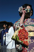 Kimono-clad 20-year-old Japanese men watch another watch another newly anointed adult woman take a photo  after attending  a ceremony held for Coming-of-Age Day in Shimoda, Shizuoka Prefecture, Japan. While Japanese women can marry as early as 16 years of age and men at 18, neither is considered to reach adulthood until they reach 20, when they can also legally begin to smoke, drink and vote.ey can also legally begin to smoke, drink and vote.