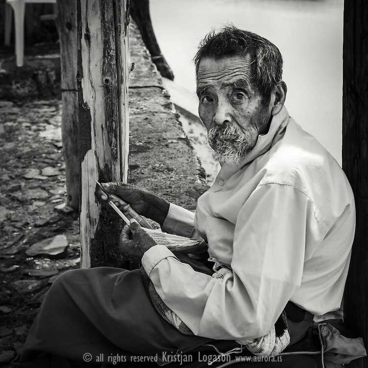 Old man sitting out in the street of Janitzio knitting