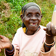 Mukagahima, an elderly Twa, or pygmy, woman with polydactylism, holds a glass of safe drinking water near Kisaro Community Clinic in Kisaro Sector, Rulindo District, Rwanda.