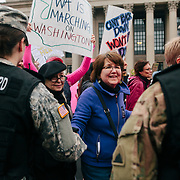 Protestors shake hands with women National Guard members while marching in the Women's March on Washington D.C., January 21, 2017