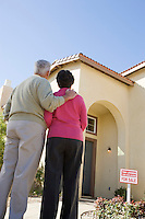 Senior couple examining exterior of house put on sale