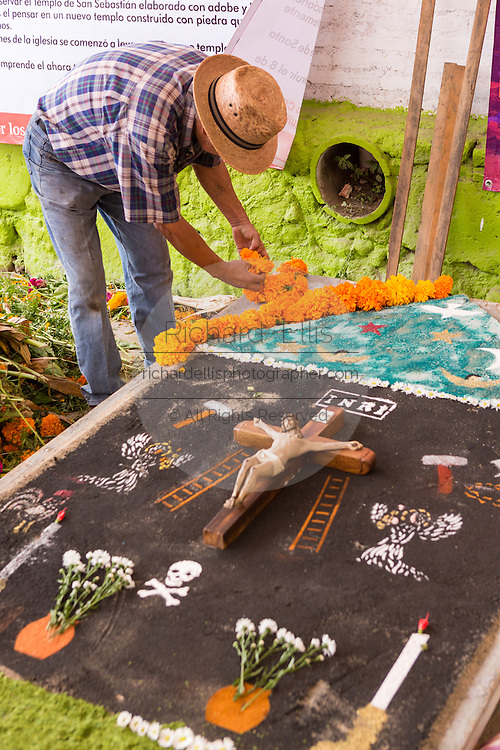 Mexican artists create elaborate sand painting during the Day of the Dead festival known in spanish as Día de Muertos at the old cemetery October 31, 2014 in Xoxocotlan, Mexico.