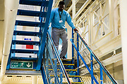 A prisoner walking down the stairs on Benbow wing inside HMP/YOI Portland, a resettlement prison with a capacity for 530 prisoners. Dorset, United Kingdom.