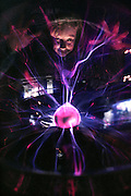Static electricity. A child plays with a plasma globe in a museum. A plasma globe is a large glass vessel, containing a gas at low pressure. A voltage of static electricity is applied between the metal sphere at centre and the glass. Static discharge across the gas causes its atoms to lose their electrons, a 'plasma' state. When the nuclei and their electrons recombine, they emit a characteristic color light. Placing an object against the glass, such as the child's hand, concentrates the local static charge and creates the beautiful 'streamer' effect seen here. Photographed at the Boston Museum of Science. MODEL RELEASED (1991)