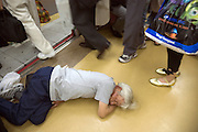 homeless man sleeping on the floor of a commuter train with passengers exciting Japan