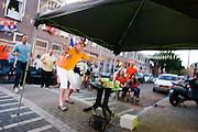 Bewoners van de Violenstraat in de Utrechtse volkswijk Ondiep, de wijk waar Wesley Sneijder vandaan komt, kijken op een scherm naar de WK finale van Nederland tegen Spanje.<br /> <br /> A supporter is yelling at the screen when he is watching the finals of the World Championship Soccer 2010 on the street in the Utrecht district Ondiep.