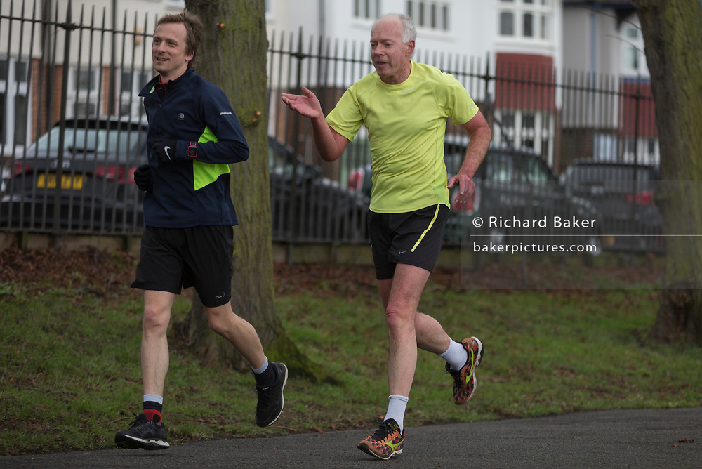 A middle-aged gentleman and a younger running companion jog through Ruskin Park in Lambeth, on 9th February 2018, in London, England.