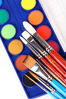 Paint box and brushes on white background
